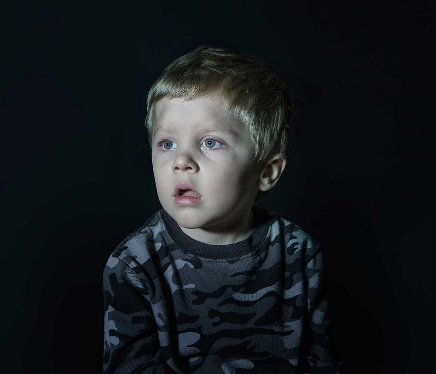 Portrait of a boy vacantly staring. He is engrossed in TV.