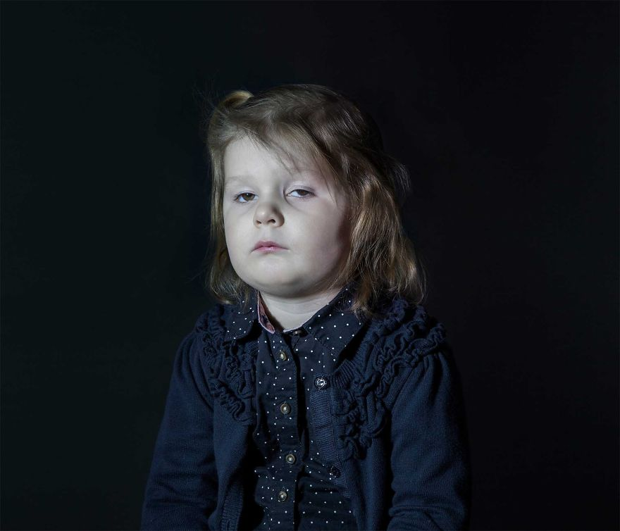 Portrait of a girl in blue sweater with dotted shirt vacantly staring. She is engrossed in TV.