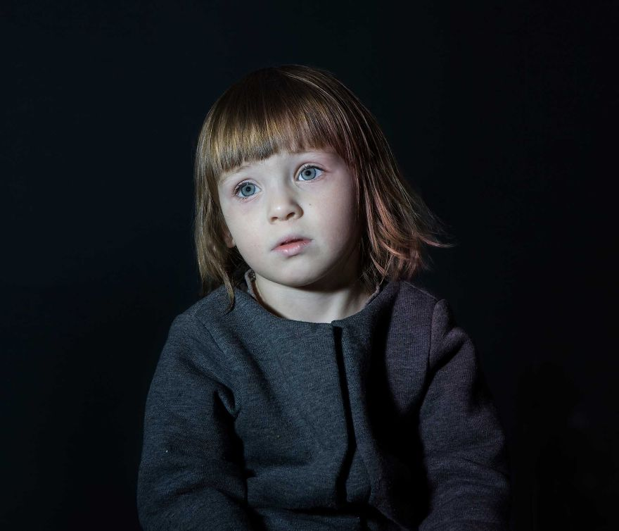 Portrait of girl in grey jacket vacantly staring. She is engrossed in TV.